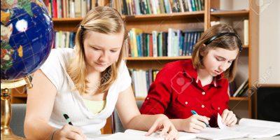 Teenage girls studyng, doing homework in school library.